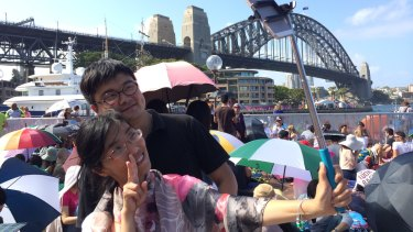 Jonas Cai and wife Freya Cai take a photo with a selfie stick at The Rocks on New Year's Eve.