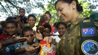 Corporal Aspen Williams hands out Christmas presents to local children presents for Christmas in a small village on the out skirts of Honiara.