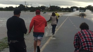 People rush to try and save the occupants of a car swept away in Maitland.
