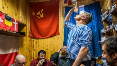 Russian and Chilean researchers drink homemade vodka at the Bellingshausen Station on King George Island in Antarctica.