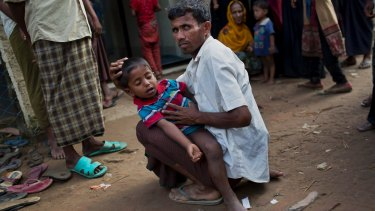 A Rohingya Muslim man holds a child with fever