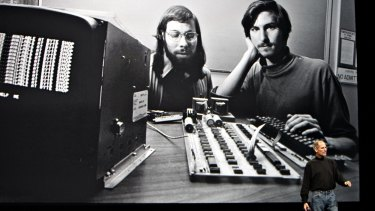 Steve Jobs speaks in 2010 before an image of himself and Steve Wozniak with the Apple I Computer they made from borrowed Atari parts.