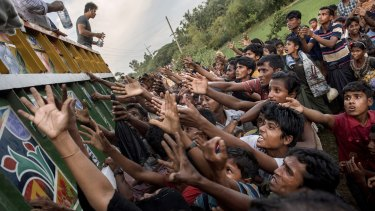 Rohingya reach out to collect food and water rations at a refugee camp in Bangladesh.