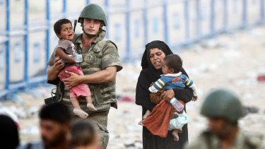 A Turkish soldier carries a Syrian child as they walk to cross into Turkey at Akcakale border gate on Monday.