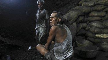 Workers take break at a coal wholesale market in Mumbai, India.
