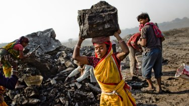 Local villagers work to scavenge coal illegally from an open-cast coal mine in the village of Jina Gora near Jharia, India.