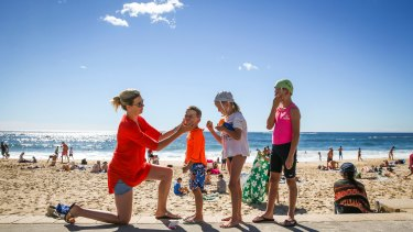 Kate Swift and her three children Carter, 5, Willow, 7, and Finn, 9, apply sunscreen at Coogee Beach.