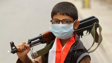 A boy holds a machine gun in Sanaa, Yemen, ahead of a sandstorm.