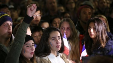 Women sing the French national anthem at a vigil in Sydney following the attack in Nice.