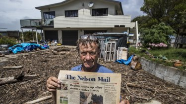 John Painton of Ruby Bay, pictured with a copy of the Nelson Mail front page from January 13 1997 with the last major storm. He said this was worse.
