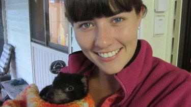 Biologist Emma Peel with a young Tasmanian devil.