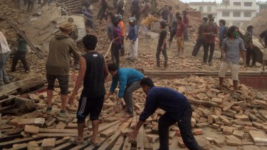 Rescuers at the site of a Kathmandu building that collapsed after Saturday's earthquake in Nepal.