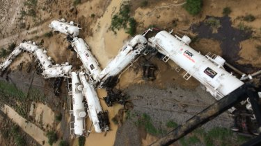 An Aurizon freight train lies beside the tracks after derailing near Julia Creek in Queensland's north-west.