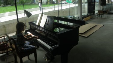 Silke Bulow's daughter Nina at the piano in the shared common room at their apartment block.