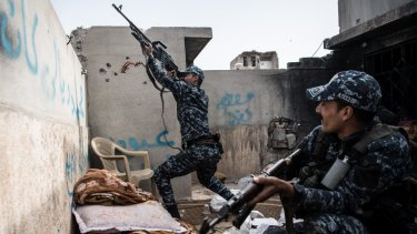 An Iraqi policeman fires a machine gun at an Islamic State position on a nearby rooftop.