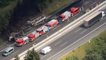 An aerial view shows the site of the accident and the burnt-out bus.