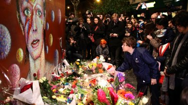 A boy leaves flowers beneath a mural of David Bowie in Brixton.