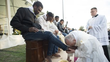 Pope Francis kisses the foot of a man during the foot-washing ritual at the Castelnuovo di Porto refugee centre near Rome on Thursday.