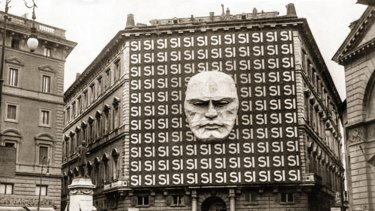 """National Fascist Party headquarters, Rome, 1934, decorated with Benito Mussolini's face and the word Si in reference to the Italian general election which took place in the form of a referendum; voters could either accept or reject the Grand Council of the National Fascist Party, 99.84 per cent of voters voted """"si""""."""