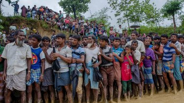 Rohingya Muslim men, who crossed over from Myanmar into Bangladesh, wait for their turn to collect food.