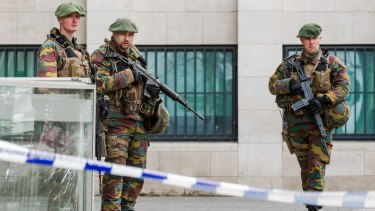 Soldiers stand guard as terror suspect Salah Abdeslam appears in court at a justice building in Brussels in April.