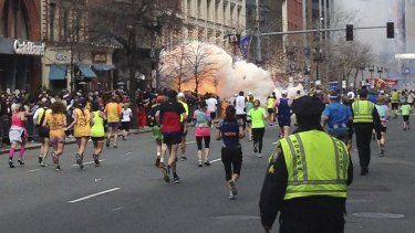 Runners continue towards the finish line of the Boston Marathon as a bomb detonates.