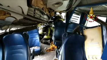 Italian firefighters try to help a passenger out after the train derailed.