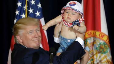 The final stretch: Donald Trump on stage with six-month-old Catalina Larkin in Florida.