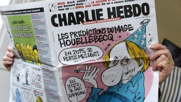 A person reads the latest issue of the French satirical newspaper Charlie Hebdo in Paris after gunmen armed with Kalashnikovs opened fire in the offices of the weekly magazine in Paris.