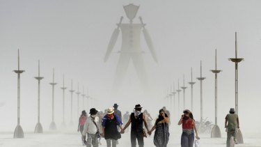 Burning Man participants walk through dust at the annual Burning Man event on the Black Rock Desert in 2014.