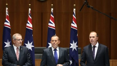 There's a boom: Mr Morrison, Mr Abbott and Mr Dutton wait for a roundtable meeting.