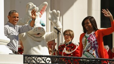 President Barack Obama and first lady Michelle Obama wave to visitors from the Truman Balcony during the White House Easter Egg Roll on the South Lawn of the White House.