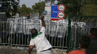 A migrant throws a bottle toward Hungarian police at the 'Horgos 2' border crossing into Hungary.