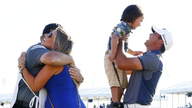 Jason Day celebrates with his son Dash, wife Ellie and caddie Colin Swatton.