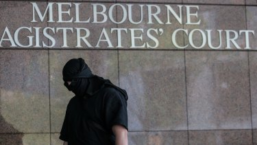 A hooded man arrives at Court to support the  five  alleged terror suspects on Thursday.