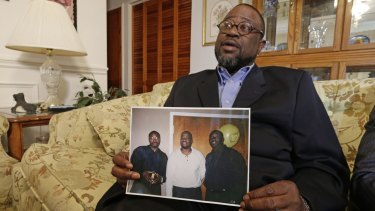 Anthony Scott holds a photo of himself, centre, and his brothers Walter (left) and Rodney, at his home near North Charleston, South Carolina.