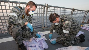 Able Seaman Marine Technicians Bryce Williams (left) and Ryan Kimber remove the outer packing from seized parcels of heroin on the flight deck of HMAS Warramunga on January 24.