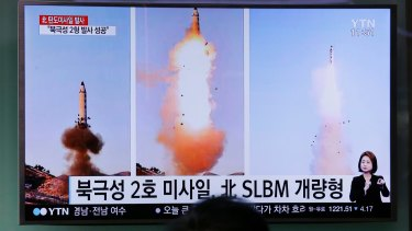 """A man watches a TV news program showing photos published in North Korea's Rodong Sinmun newspaper of North Korea's """"Pukguksong-2"""" missile launch, at Seoul Railway station."""