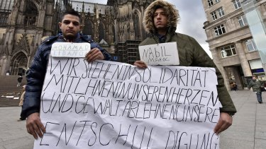 "Mohamad of Lebanon, left, and Nabil of Morocco hold a banner in front of the Cologne cathedral to apologise for other migrants' crimes. The sign reads ""we stand in solidarity in our hearts with you, we refuse  violence and hope you accept our apologize""."