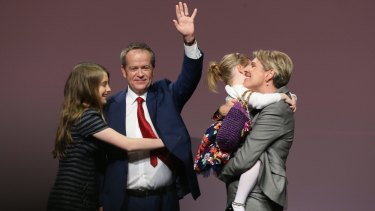 Opposition Leader Bill Shorten is hugged by his daughter Georgette as his other daughter Clementine embraces Deputy Opposition Leader Tanya Plibersek after the ALP National Conference on Friday.