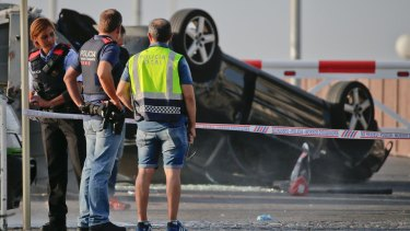 Police officers stand near an overturned car at the spot where terrorists were intercepted by police in Cambrils on Friday.