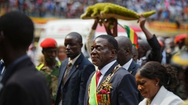 """Mnangagwa, center, known as """"The Crocodile"""" for his ruthlesness, and his wife Auxillia, right, leave the stadium as a supporter holds a stuffed crocodile behind."""