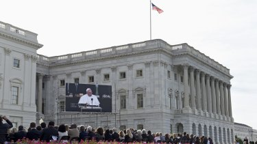 A crowd of about 50,000 people watch Pope Francis on a large screen television from the West Front of the Capitol in Washington.