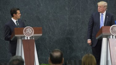 Mexican President Enrique Pena Nieto, left, looks at Donald Trump during a press conference in Mexico City.