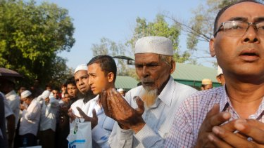Myanmar Muslims pray on Monday as they bury the body of Ko Ni, who was assassinated on Sunday.