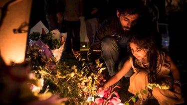 Adnan Amjid, friend and housemate of Zeeshan Akbar, helps a girl light a candle at a vigil.