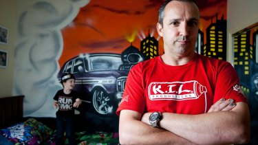 Commercial graffiti artist Ashley Goudie (right) and three-year-old Braxton Vella (left) with the vintage GT Ford Falcon Goudie painted in Braxton's Melton bedroom.