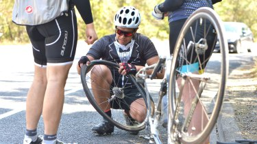 Cholo Santos fixes his punctured tyre during a stop the tacks protest ride in Kew.