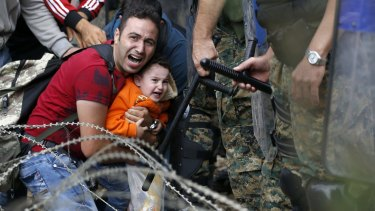 A migrant holding a boy reacts as they are stuck between Macedonian riot police and fellow migrants during a clash in northern Greece.