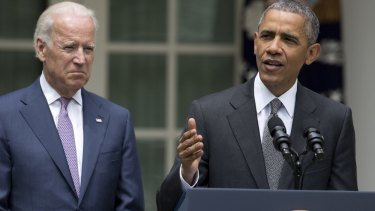 Major victory for his legacy ... President Barack Obama (right), accompanied by Vice-President Joe Biden, talks about the US Supreme Court's decision to protect the Affordable Care Act.
